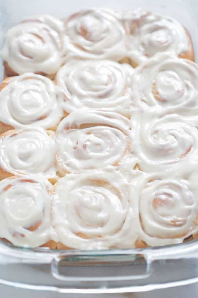 12 overnight cinnamon rolls that have been baked and are covered with cream cheese frosting