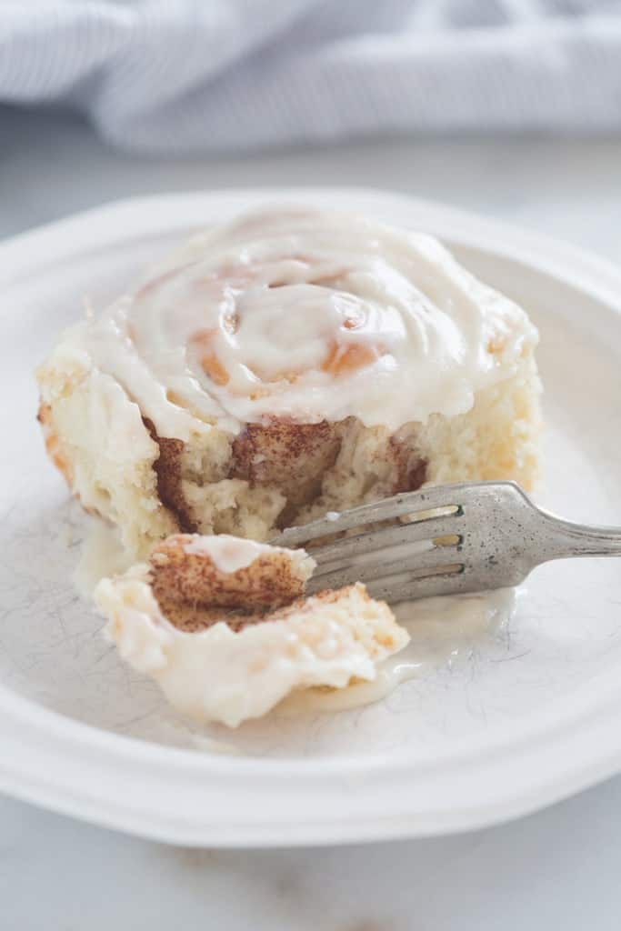 A cinnamon roll on a white plate with a fork cutting a piece of it.