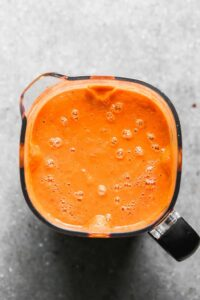 A blender with pureed, roasted tomato soup in it.