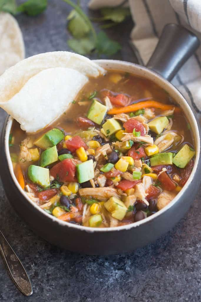 A tortilla dipped in Slow Cooker Chipotle Chicken Fajita Soup.