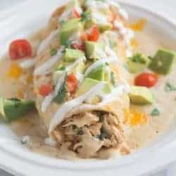 Smothered Ranch Chicken Burritos - delicious burritos, baked until crisp and then smothered in a creamy homemade ranch sauce.   Tastes Better From Scratch