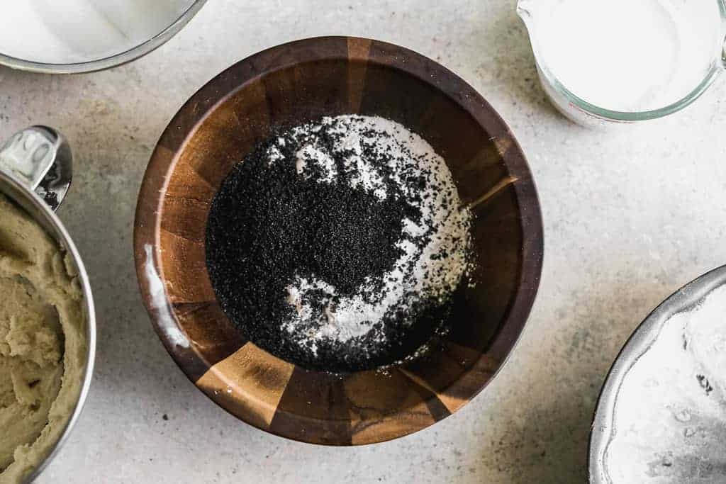A wooden mixing bowl with flour, salt, baking powder and poppyseeds.