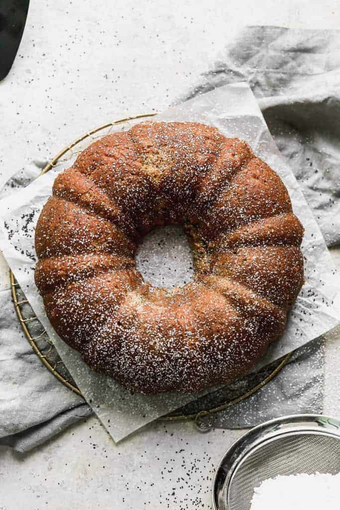 Overhead photo of a baked poppy seed cake dusted with powdered sugar.