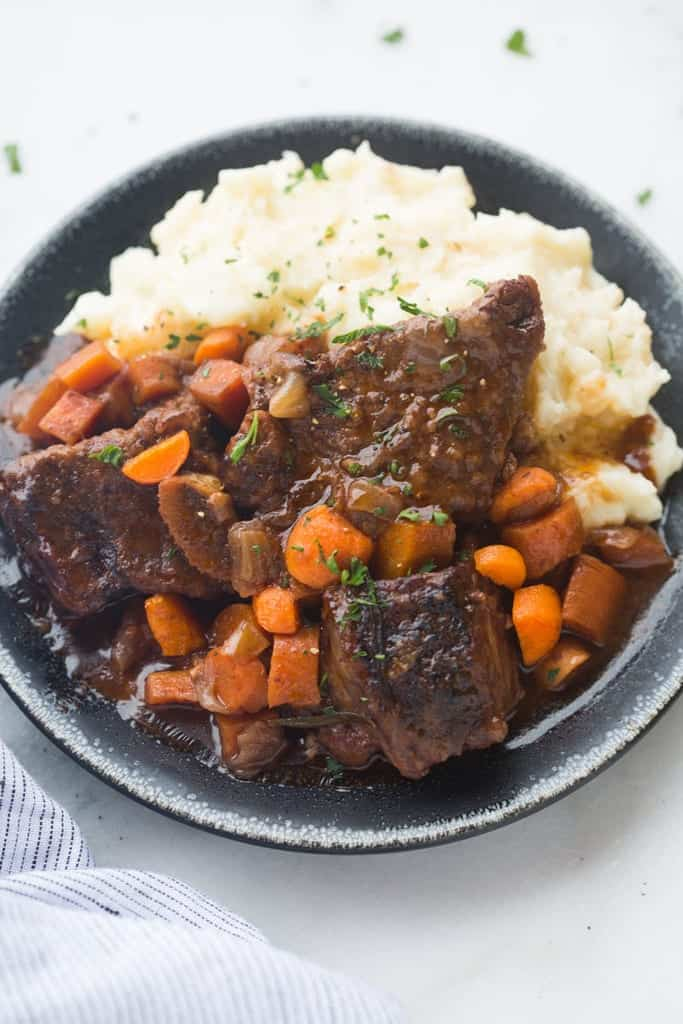 A plate filled with short ribs, vegetables, and mashed potatoes.