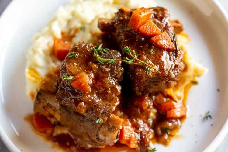 Two braised short ribs and mashed potatoes on a white plate.