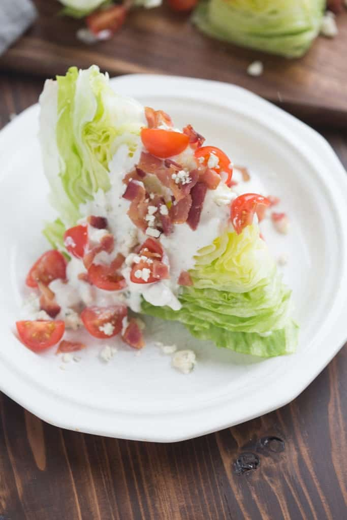 Classic Wedge Salad with bacon, tomatoes and a creamy, insanely delicious homemade blue cheese dressing! |