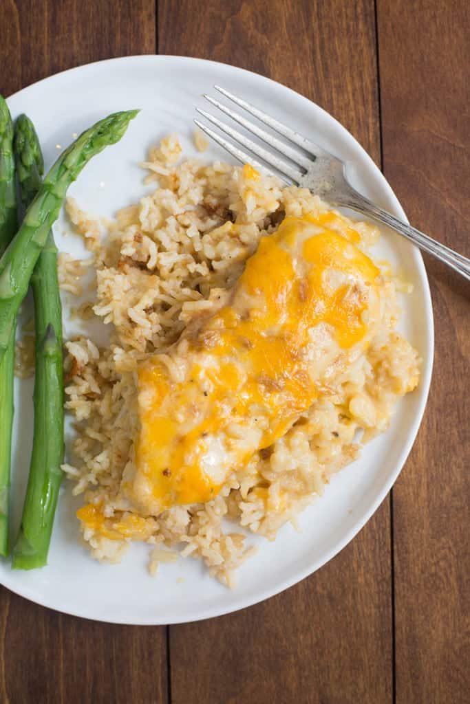 Cheesy Chicken on top of long grain Rice with asparagus on a white plate.
