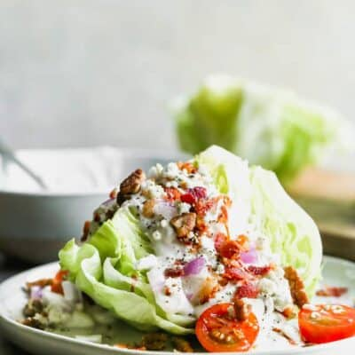 A wedge salad on a plate, topped with blue cheese dressing, bacon crumbles, tomato, and onion.