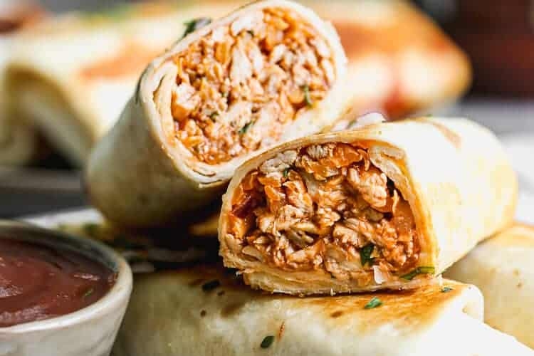 A BBQ chicken wrap cut in half to show the filling inside the tortilla, stacked with other wraps on a plate.