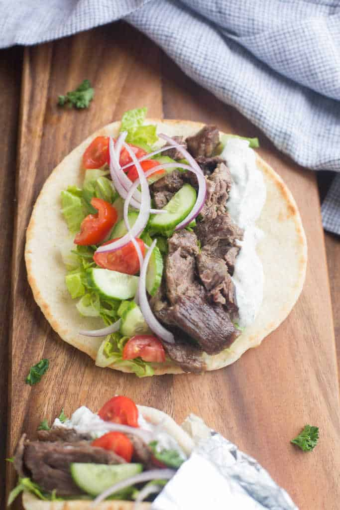 A pita filled with beef gyro, sauce, lettuce, cucumber, tomato, red onion.