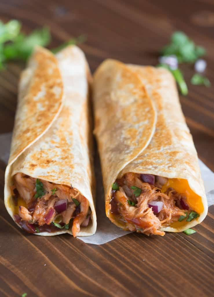 BBQ chicken wraps laying side by side on a wooden board.