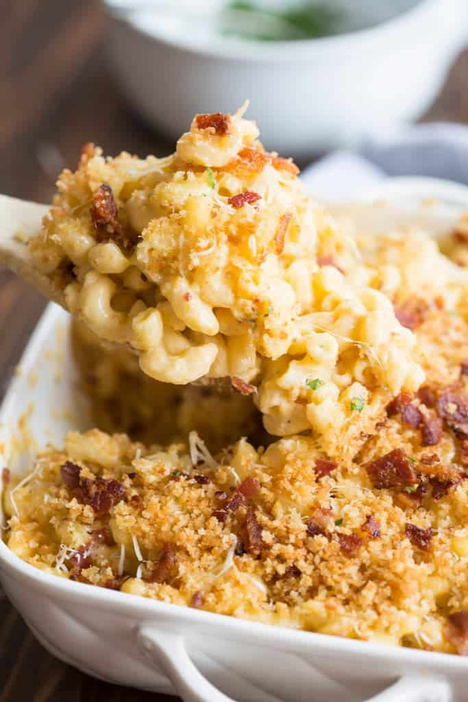 A wooden spoon taking Gourmet Baked Mac and Cheese out of a casserole dish.