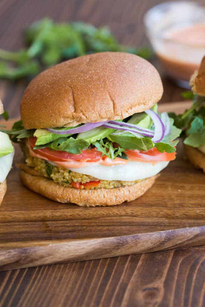 A quinoa veggie burger on a wheat bun with tomato, lettuce, avocado, and onion.
