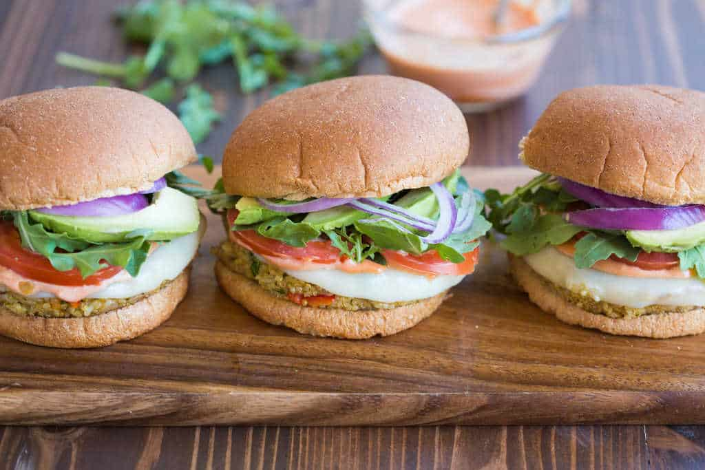 Three veggie quinoa burgers on a wooden board.
