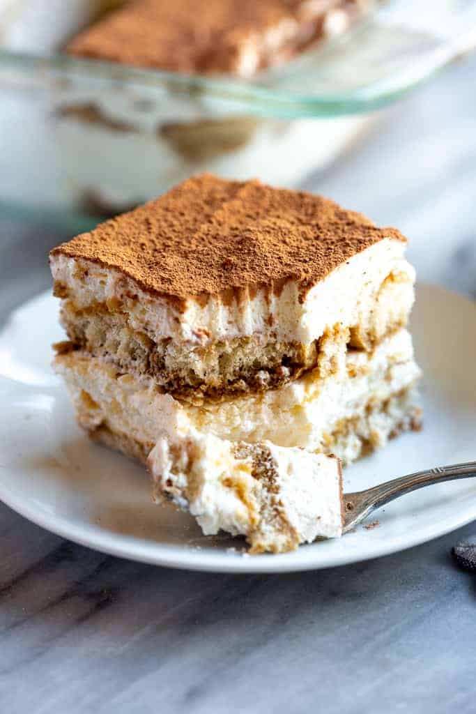 A piece of tiramisu with a bite take out with a fork.