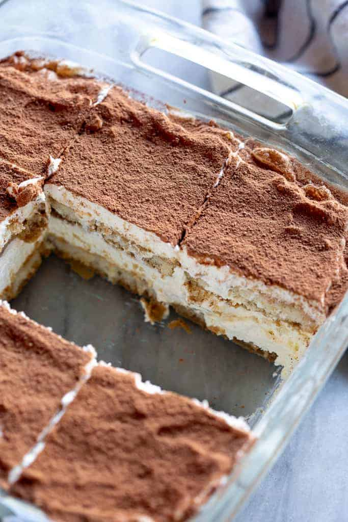 A clear glass pan of tiramisu with two slices removed from the center.