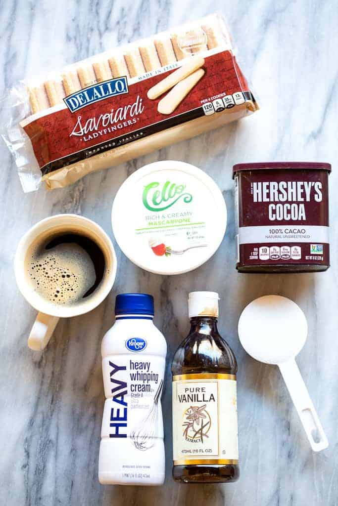 The ingredients needed for tiramisu including ladyfingers, espresso, mascarpone, cocoa powder, cream, vanilla and sugar.