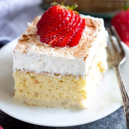 A slice of Tres Leches Cake with a sliced strawberry on top, served on a plate.