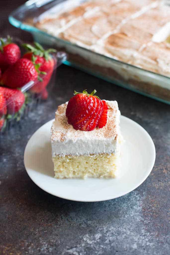 A slice of Tres Leches cake on a white plate topped with whipped cream and strawberries with strawberries and a full cake in the background.