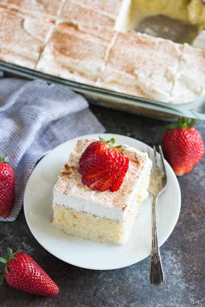 A Slice Of Tres Leches Cake On White Plate With Fork Strawberries Surround