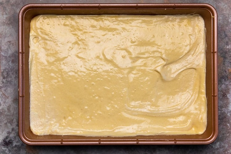 Cake batter smoothed into a 9x13 inch baking pan.