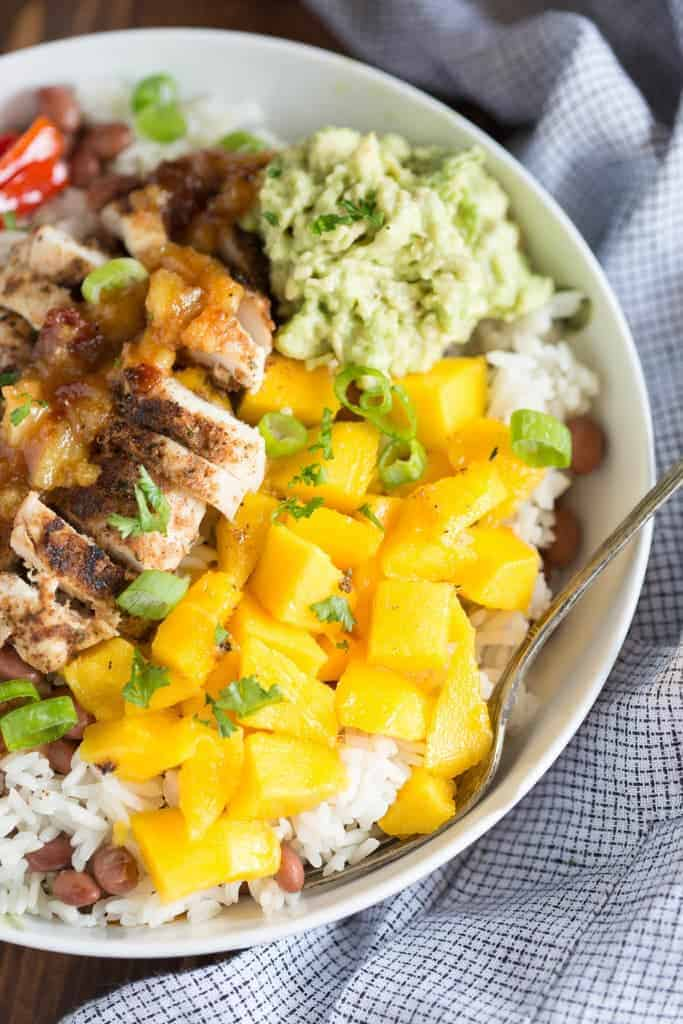 Mango, mashed avocado, bell peppesr and jerk seasoned chicken on top of coconut rice and red beans. T