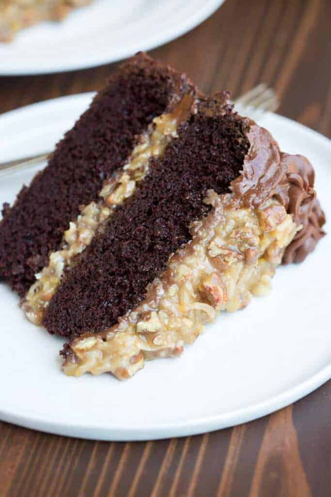 A slice of German Chocolate Cake served on a plate, with two layers of chocolate cake, and German chocolate frosting.