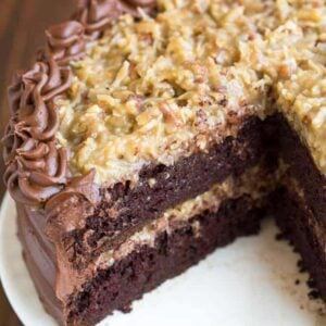 A double layer German Chocolate Cake with coconut pecan frosting, with a slice taken out of it.