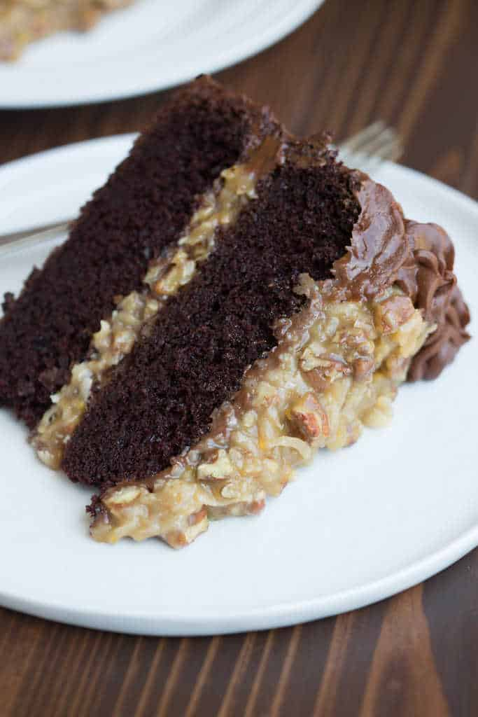 A Large Slice Of German Chocolate Cake Laying Sideways On White Plate
