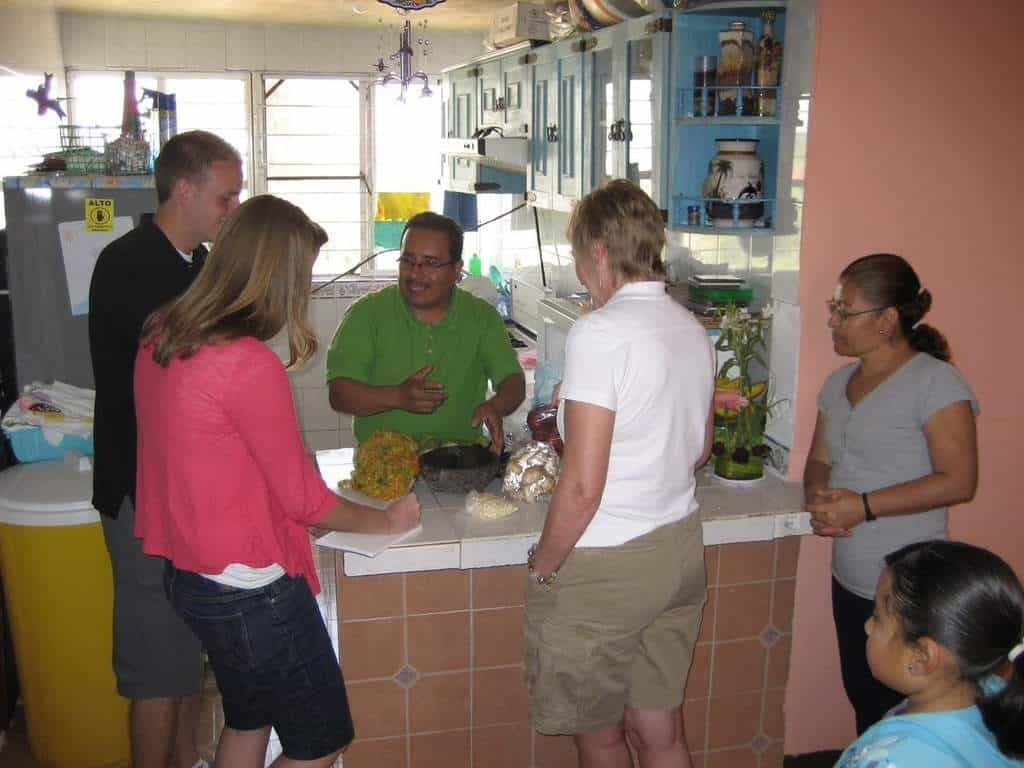 Four people surrounding a counter where a man is explaining how to cook Mexican rice.