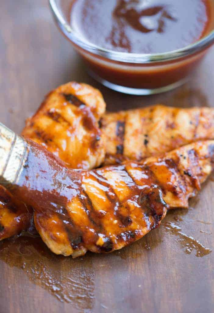Homemade BBQ Sauce being spread on grilled chicken tenders.