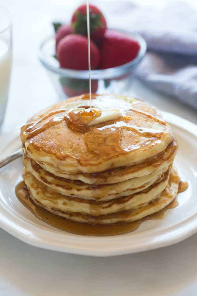 Syrup being poured on a large stack of homemade buttermilk pancakes.