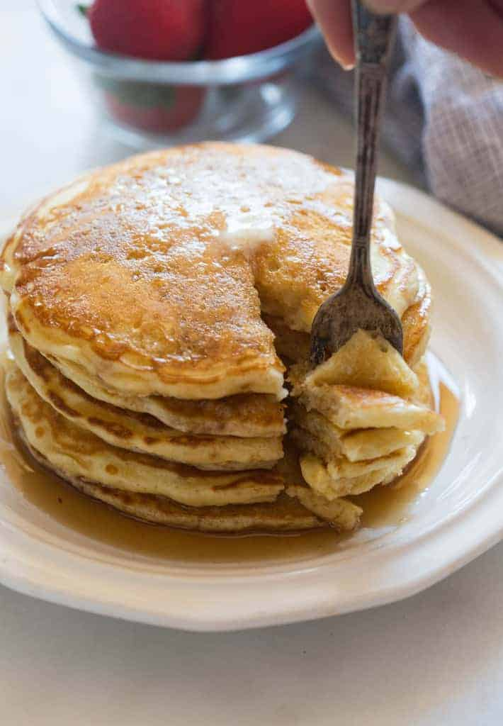 A fork removing a bite from a stack of homemade buttermilk pancakes!