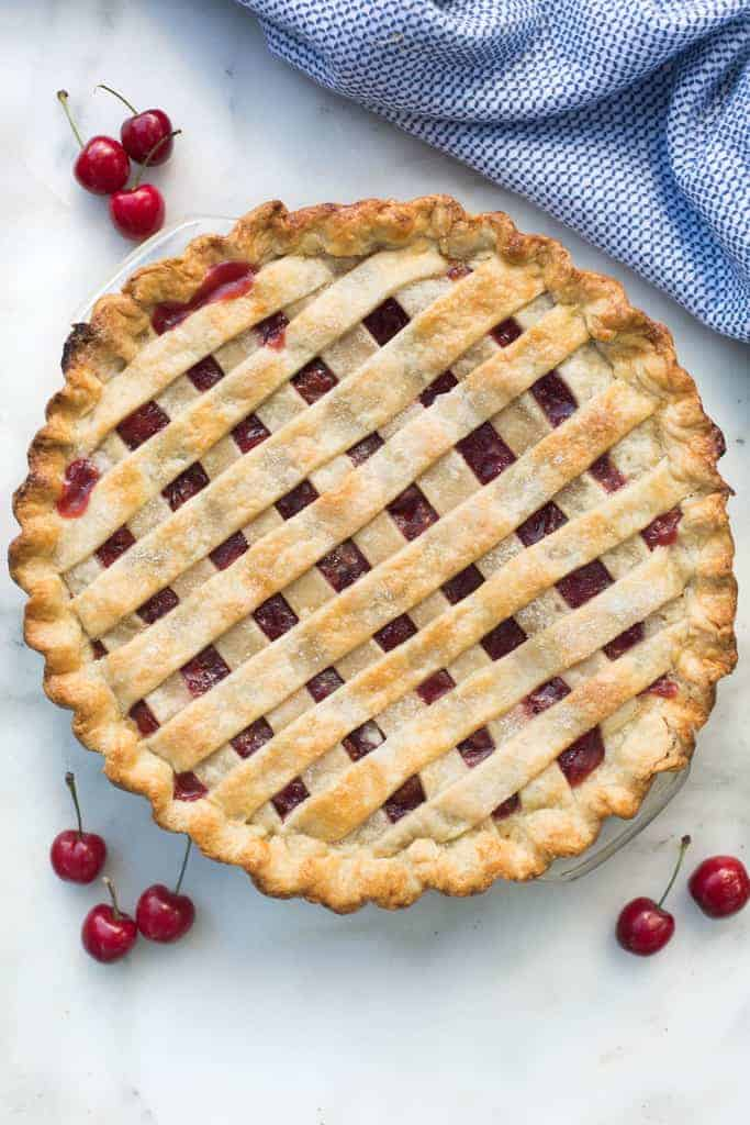 An overhead view of a homemade cherry pie with a lattice crust and surrounded by fresh cherries.