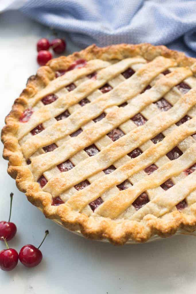 A close up of a cherry pie with a lattice crust that has been baked and is ready to eat.