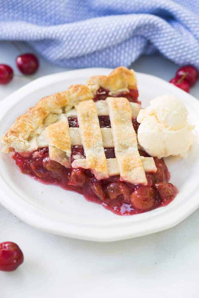 A slice of cherry pie with a scoop of vanilla ice cream on a white plate.