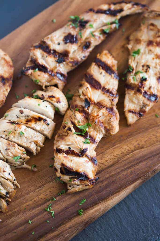 Grilled and marinated chicken tenders on a wooden board.