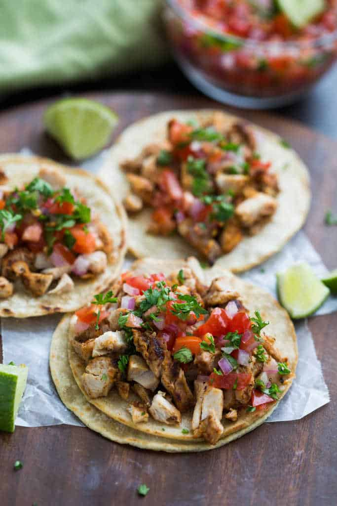 Two corn tortillas topped with grilled chicken and pico de gallo and surrounded by slices of lime.