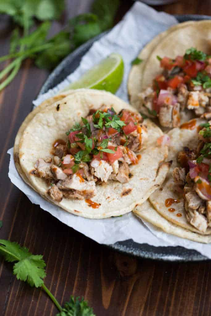 A platter of tacos with doubled corn tortillas topped with chopped grilled chicken and pico de gallo.