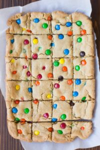 Nothing better than a big pan of thick and chewy m&m cookie bars! My favorite! | tastesbetterfromscratch.com