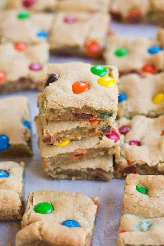 A stack of M&M Cookie bars with other cookie bars surrounding them.
