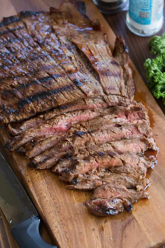 A large grilled flank steak on a cutting board with a few thin slices cut away.