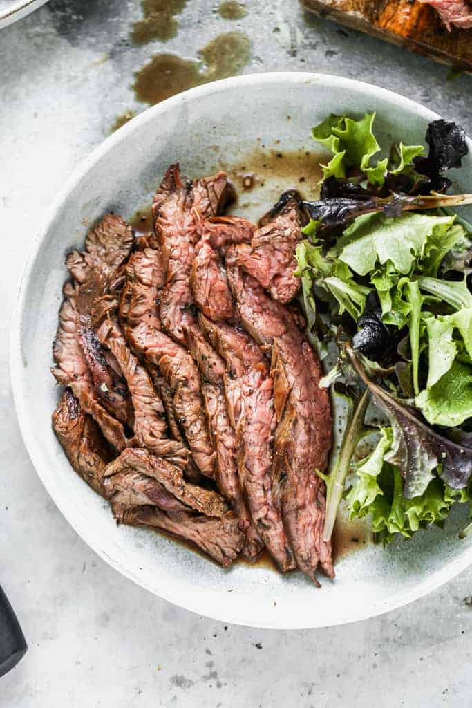 A plate with a few slices of grilled flanks steak, and a side salad.