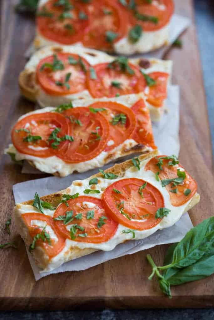 Baguettes cut in half lengthwise and widthwise and topped with Tomato, fresh Basil, and Mozzarella .