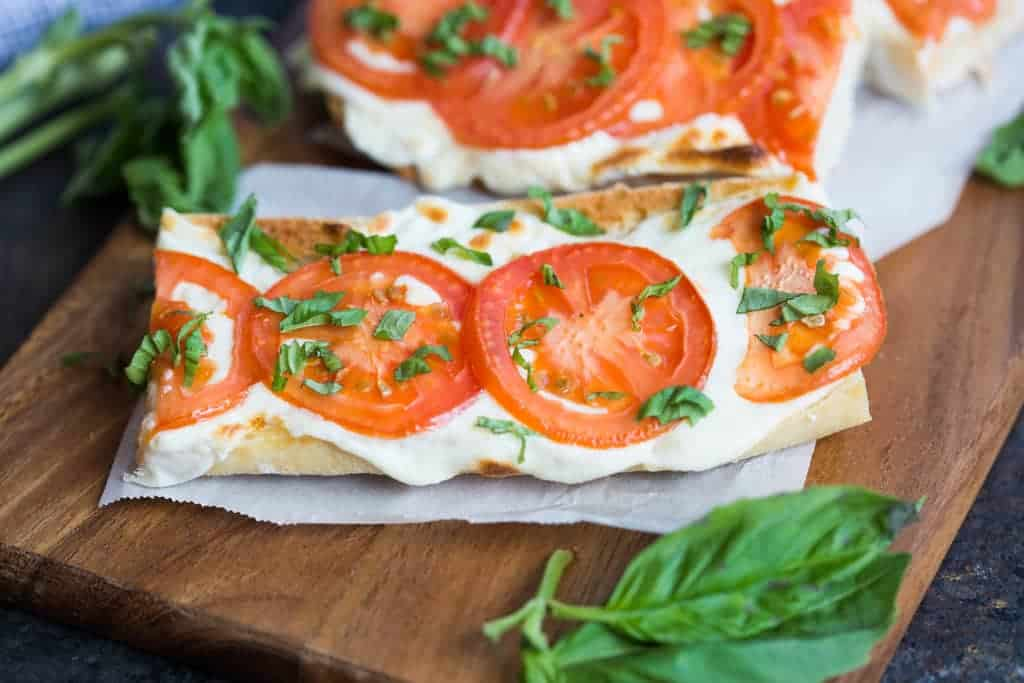 Crusty baguette toasted with fresh mozzarella cheese, tomatoes and basil. | tastesbetterfromscratch.com