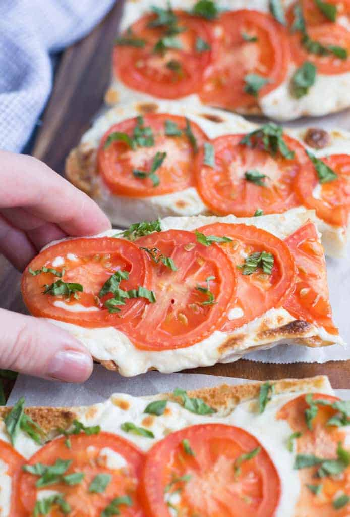 A hand reaching in to take on slice of Tomato Basil Mozzarella Toasts | tastesbetterfromscratch.com