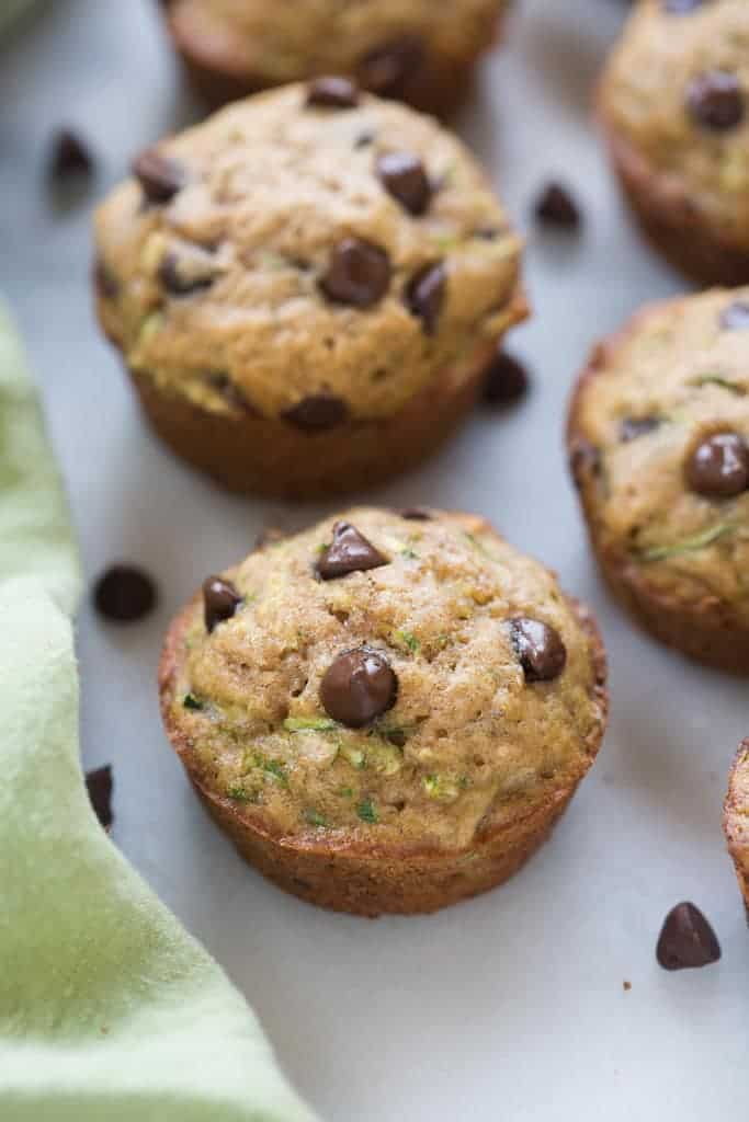 Chocolate chip zucchini muffins on a white board.