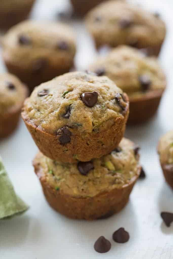 Chocolate Chip Zucchini Muffins with fresh grated zucchini, stacked on each other.