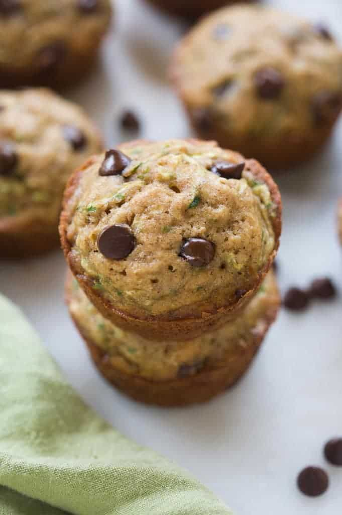 Chocolate chip zucchini muffins that are stacked on top of each other.