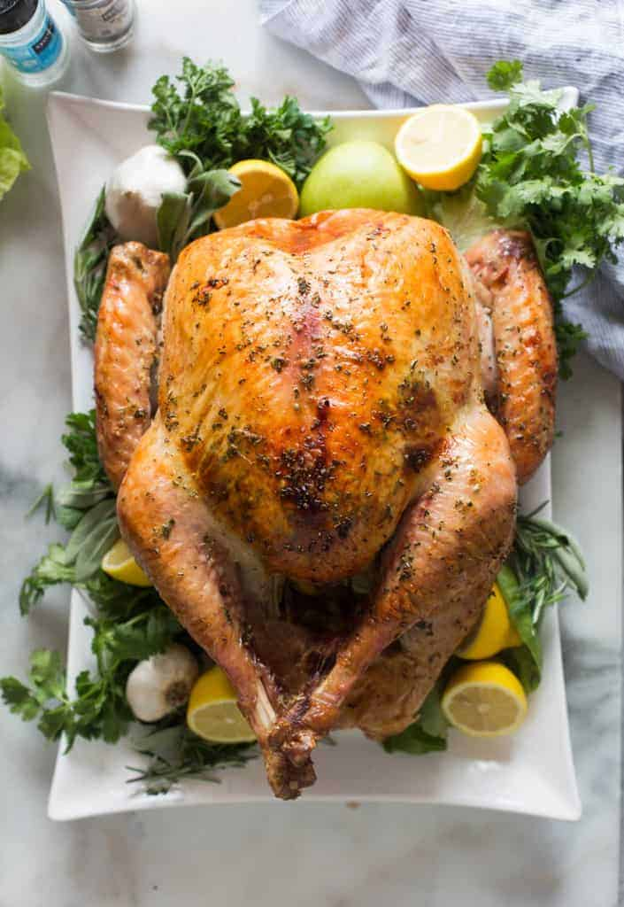 Overhead photo of a roasted turkey on a large white platter, garnished with lemons, apples, garlic and fresh green herbs.